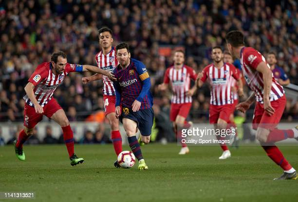 Lionel Messi of FC Barcelona competes for the ball with Diego Roberto Godin of Club Atletico de Madrid during the La Liga match between FC Barcelona...