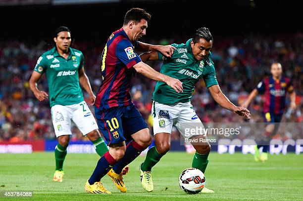 Lionel Messi of FC Barcelona competes for the ball with Edwin Hernandez of Club Leon during the Joan Gamper Trophy match between FC Barcelona and...