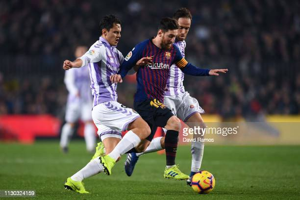 Lionel Messi of FC Barcelona competes for the ball with Enes Unal and Michel Herrero of Real Valladolid CF during the La Liga match between FC...