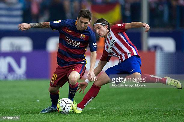 Lionel Messi of FC Barcelona competes for the ball with Filipe Luis of Atletico de Madrid during the La Liga match between Club Atletico de Madrid...