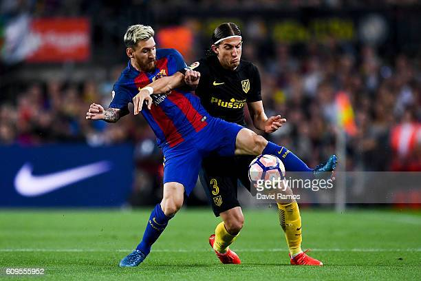Lionel Messi of FC Barcelona competes for the ball with Filipe Luis of Club Atletico de Madrid during the La Liga match between FC Barcelona and Club...