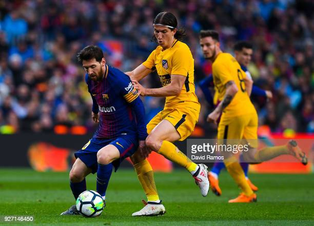 Lionel Messi of FC Barcelona competes for the ball with Filipe Luis of Club Atletico de Madrid during the La Liga match between Barcelona and...