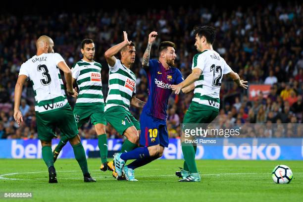 Lionel Messi of FC Barcelona competes for the ball with four Eibar players during the La Liga match between Barcelona and SD Eibar at Camp Nou on...