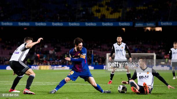 Lionel Messi of FC Barcelona competes for the ball with Gabriel and Nemanja Maksimovic of Valencia CF during the Copa del Rey semifinal first leg...