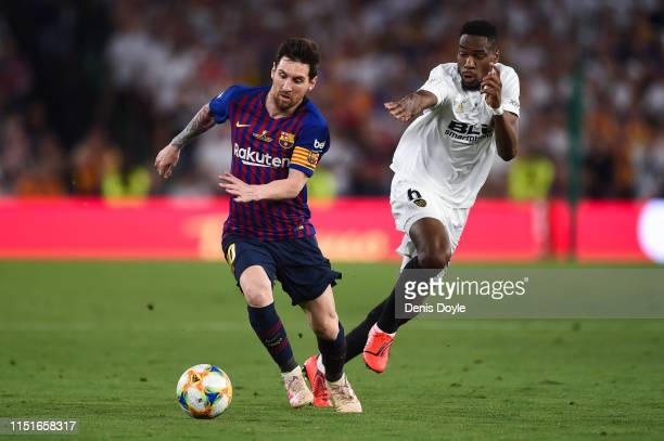 Lionel Messi of FC Barcelona competes for the ball with Geoffrey Kondogbia of Valencia CF during the Spanish Copa del Rey match between Barcelona and...