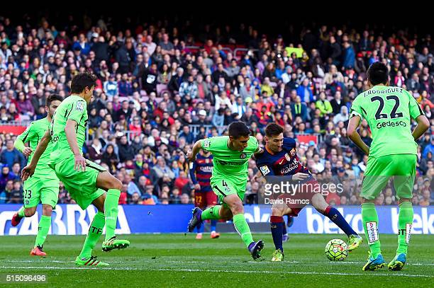 Lionel Messi of FC Barcelona competes for the ball with Getafe CF players during the La Liga match between FC Barcelona and Getafe CF at Camp Nou on...
