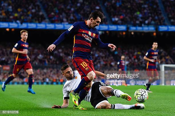 Lionel Messi of FC Barcelona competes for the ball with Guilherme Siqueira of Valencia CF during the La Liga match between FC Barcelona and Valencia...