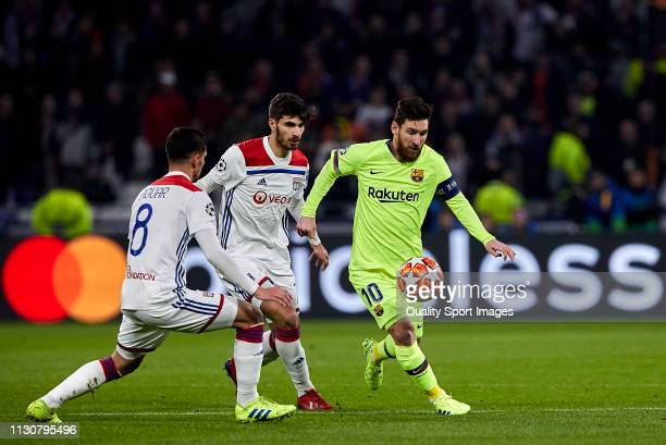 Lionel Messi of FC Barcelona competes for the ball with Houssem Aouar of Olympique Lyonnais during the UEFA Champions League Round of 16 First Leg...