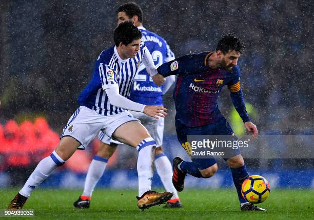Lionel Messi of FC Barcelona competes for the ball with Igor Zubeldia of Real Sociedad de Futbol during the La Liga match between Real Sociedad and...