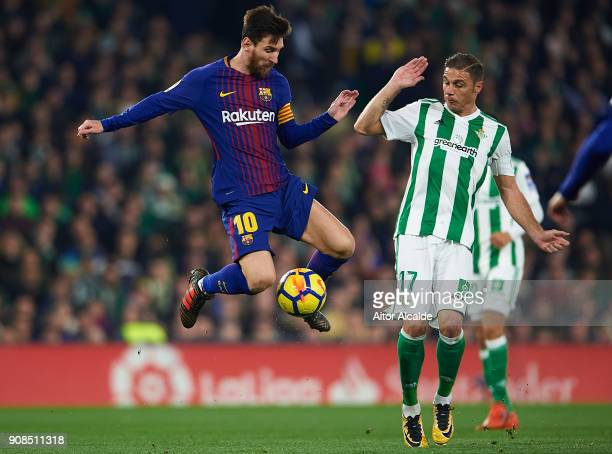 Lionel Messi of FC Barcelona competes for the ball with Joaquin Sanchez of Real Betis Balompie the La Liga match between Real Betis and Barcelona at...