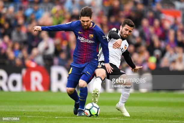 Lionel Messi of FC Barcelona competes for the ball with Jose Luis Gaya of Valencia CF during the La Liga match between Barcelona and Valencia at Camp...