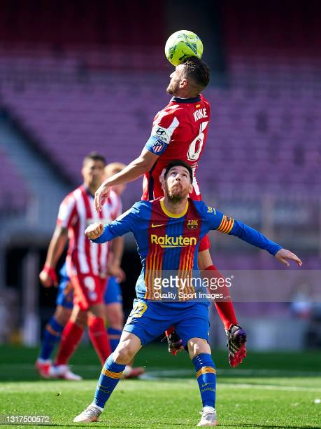 Lionel Messi of FC Barcelona competes for the ball with Koke Resurreccion of Atletico de Madrid during the La Liga Santander match between FC...