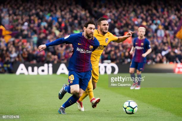 Lionel Messi of FC Barcelona competes for the ball with Koke of Atletico de Madrid during the La Liga match between Barcelona and Atletico Madrid at...