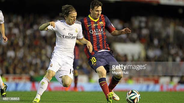 Lionel Messi of FC Barcelona competes for the ball with Luka Modric of Real Madrid CF during the Copa del Rey Final between FC Barcelona and Real...