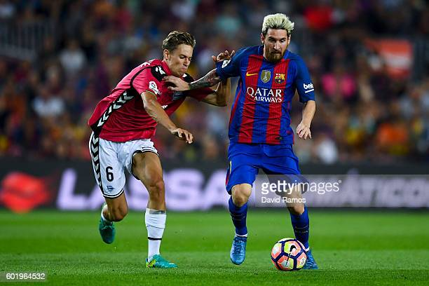 Lionel Messi of FC Barcelona competes for the ball with Marcos Llorente of Deportivo Alaves during the La Liga match between FC Barcelona and...