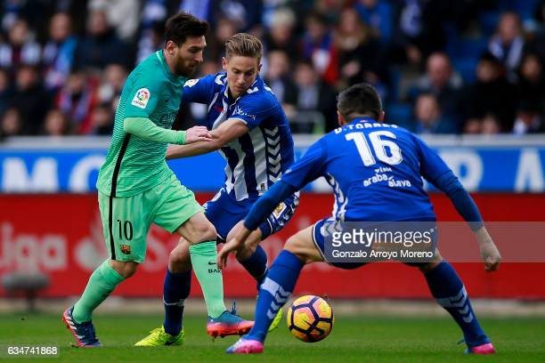 Lionel Messi of FC Barcelona competes for the ball with Marcos Llorente of Deportivo Alaves and his teammate Daniel Torres during the La Liga match...