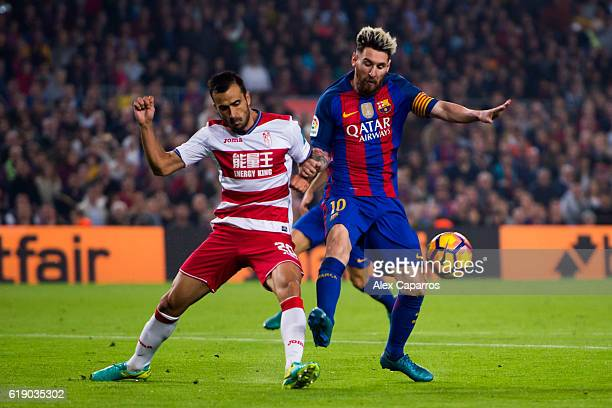 Lionel Messi of FC Barcelona competes for the ball with Matthieu Saunier of Granada CF during the La Liga match between FC Barcelona and Granada CF...