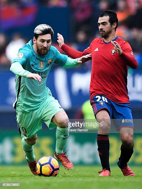 Lionel Messi of FC Barcelona competes for the ball with Miguel de las Cuevas of CA Osasuna during the La Liga match between CA Osasuna and FC...