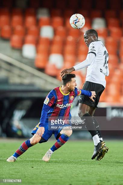 Lionel Messi of FC Barcelona competes for the ball with Mouctar Diakhaby of Valencia CF during the La Liga Santander match between Valencia CF and FC...