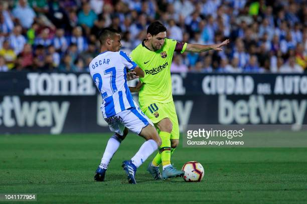 Lionel Messi of FC Barcelona competes for the ball with Oscar Rodriguez Arnaiz of Deportivo Leganes during the La Liga match between CD Leganes and...