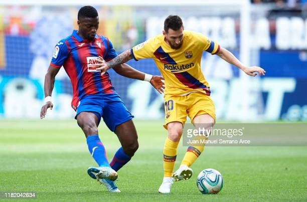 Lionel Messi of FC Barcelona competes for the ball with Papakouli Diop of SD Eibar during the Liga match between SD Eibar SAD and FC Barcelona at...