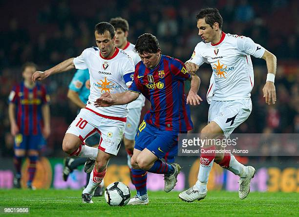 Lionel Messi of FC Barcelona competes for the ball with Patxi Pu�al and Fla�o of Osasuna during the La Liga match between Barcelona and Osasuna at...