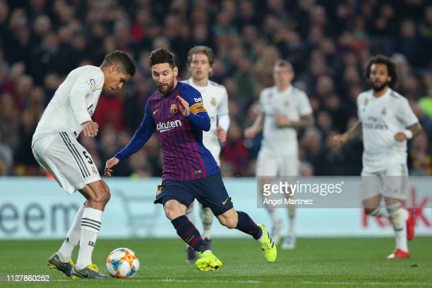 Lionel Messi of FC Barcelona competes for the ball with Raphael Varane of Real Madrid CF during the Copa del Semi Final first leg match between...