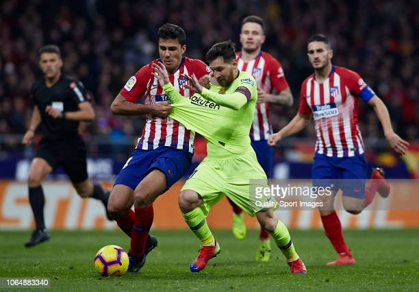 Lionel Messi of FC Barcelona competes for the ball with Rodrigo Hernandez of Atletico de Madrid during the La Liga match between Club Atletico de...