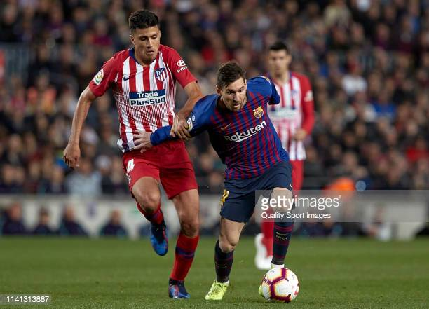 Lionel Messi of FC Barcelona competes for the ball with Rodrigo Hernandez of Club Atletico de Madrid during the La Liga match between FC Barcelona...