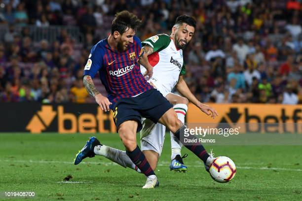 Lionel Messi of FC Barcelona competes for the ball with Ruben Duarte of Deportivo Alaves during the La Liga match between FC Barcelona and Deportivo...
