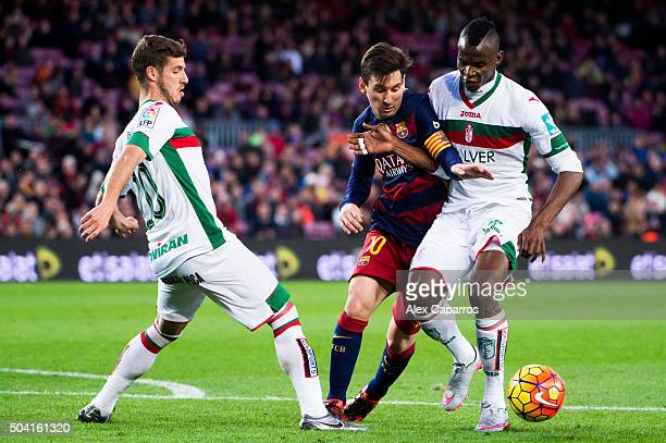 Lionel Messi of FC Barcelona competes for the ball with Ruben Perez and Uche Henry Agbo of Granada CF during the La Liga match between FC Barcelona...