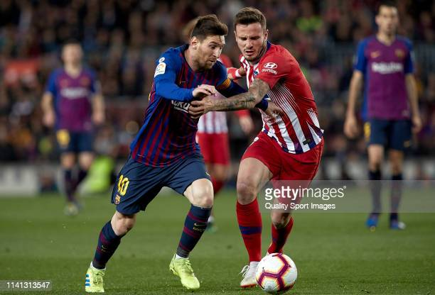 Lionel Messi of FC Barcelona competes for the ball with Saul Niguez of Club Atletico de Madrid during the La Liga match between FC Barcelona and Club...