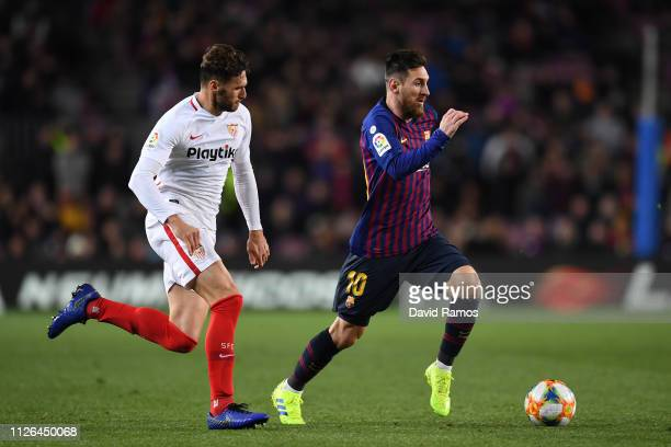 Lionel Messi of FC Barcelona competes for the ball with Sergi Gomez of Sevilla FC during the Copa del Quarter Final match between FC Barcelona and...