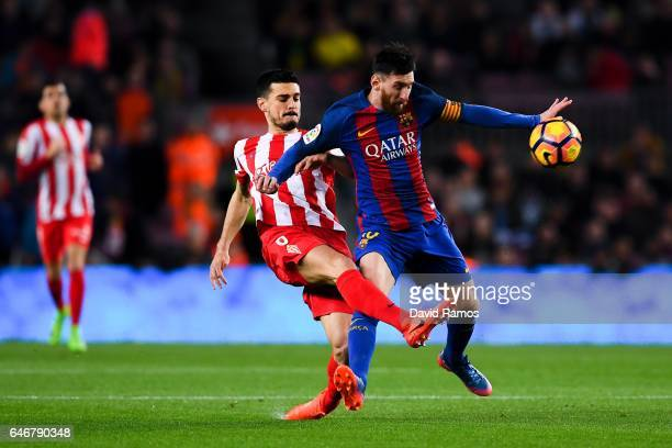 Lionel Messi of FC Barcelona competes for the ball with Sergio Alvarez of Real Sporting de Gijon during the La Liga match between FC Barcelona and...