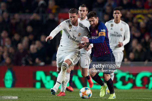 Lionel Messi of FC Barcelona competes for the ball with Sergio Ramos of Real Madrid during the Copa del Rey Semi Final first leg match between FC...