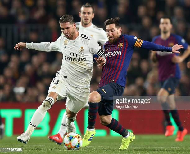 Lionel Messi of FC Barcelona competes for the ball with Sergio Ramos of Real Madrid CF during the Copa del Rey Semi Final match between FC Barcelona...