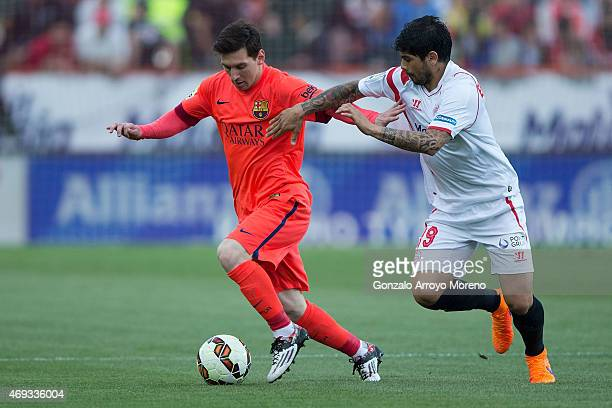 Lionel Messi of FC Barcelona competes for the ball with Sergio Rico of Sevilla FC during the La Liga match between Sevilla FC and FC Barcelona at...