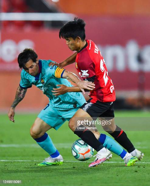Lionel Messi of FC Barcelona competes for the ball with Takefusa 'Take' Kubo of RCD Mallorca during the Liga match between RCD Mallorca and FC...