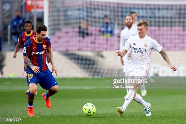 Lionel Messi of FC Barcelona competes for the ball with Toni Kroos of Real Madrid CF during the La Liga Santander match between FC Barcelona and Real...