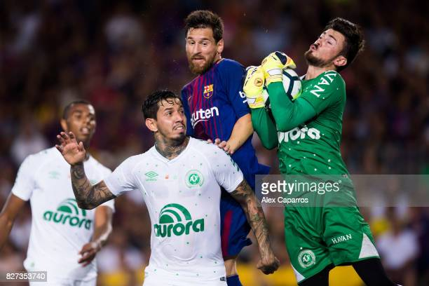 Lionel Messi of FC Barcelona competes for the ball with Victor Ramos and Elias Curzel of Chapecoense during the Joan Gamper Trophy match between FC...