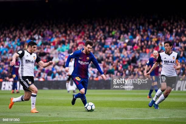Lionel Messi of FC Barcelona conducts the ball between Goncalo Guedes and Daniel Parejo of Valencia CF during the La Liga match between Barcelona and...