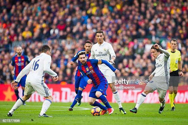 Lionel Messi of FC Barcelona conducts the ball between Mateo Kovacic Cristiano Ronaldo and Luka Modric of Real Madrid CF during the La Liga match...
