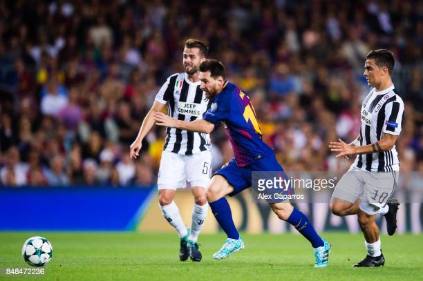 Lionel Messi of FC Barcelona conducts the ball between Miralem Pjanic and Paulo Dybala of Juventus during the UEFA Champions League group D match...