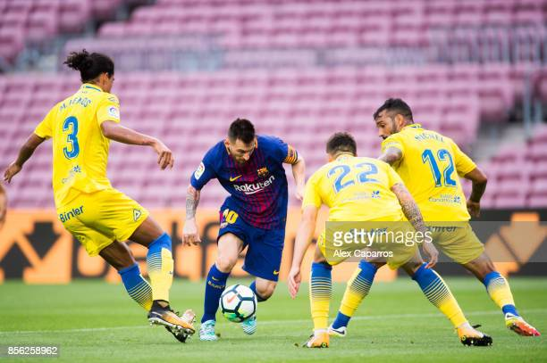 Lionel Messi of FC Barcelona conducts the ball between Pablo Lemos Ximo Navarro and Michel Macedo of UD Las Palmas during the La Liga match between...