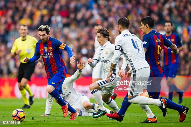 Lionel Messi of FC Barcelona conducts the ball next to his teammate Luis Suarez and Luka Modric and Sergio Ramos of Real Madrid CF during the La Liga...