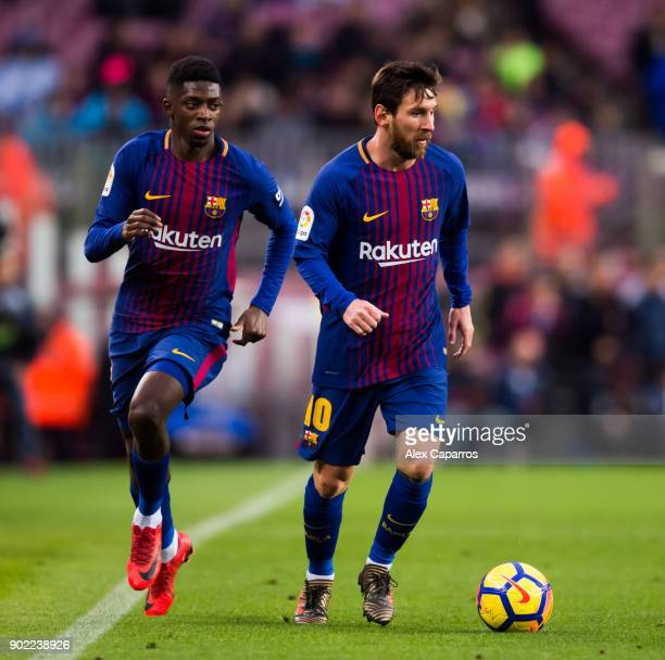 Lionel Messi of FC Barcelona conducts the ball next to his teammate Ousmane Dembele during the La Liga match between Barcelona and Levante at Camp...