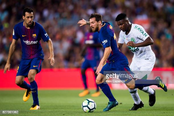 Lionel Messi of FC Barcelona conducts the ball next to Moises Ribeiro of Chapecoense during the Joan Gamper Trophy match between FC Barcelona and...