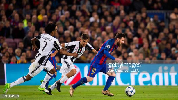 Lionel Messi of FC Barcelona conducts the ball past Juan Cuadrado and Paulo Dybala of Juventus during the UEFA Champions League Quarter Final second...