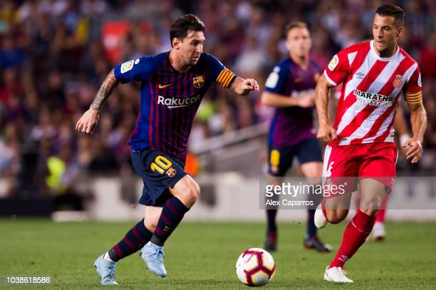 Lionel Messi of FC Barcelona conducts the ball under pressure from Alex Granell of Girona FC during the La Liga match between FC Barcelona and Girona...