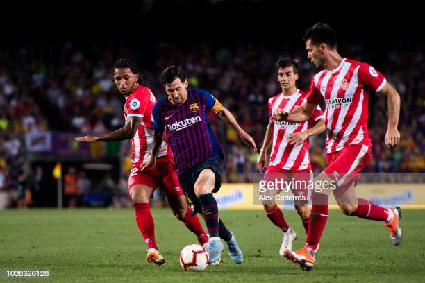 Lionel Messi of FC Barcelona conducts the ball under pressure from Douglas Luiz and Pedro Alcala of Girona FC during the La Liga match between FC...